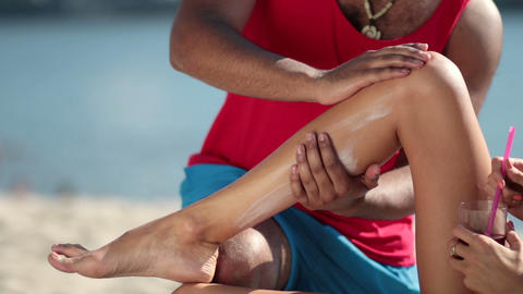 Closeup man's hand applying sunscreen on woman leg Filmmaterial
