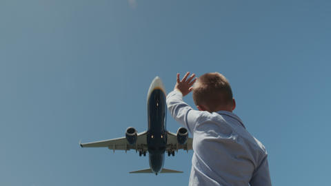 Child waving hand to the plane overhead Footage