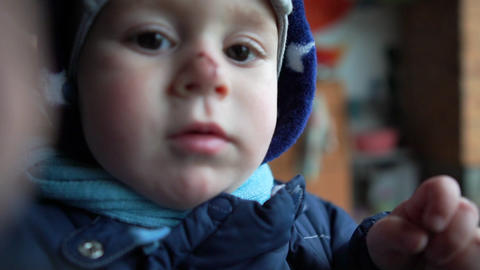 Cheery kid with a dirty nose standing in a tiny shop in spring in slow motion Live Action