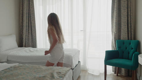 Teenager girl lying to bed and looking mobile phone rear view. Young girl Live Action