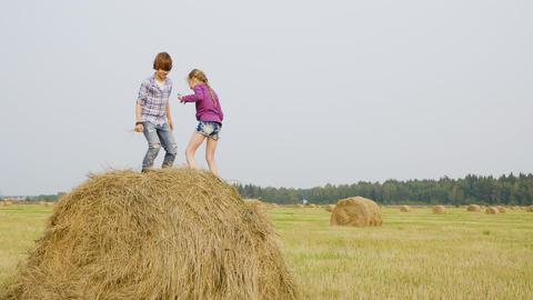 Teenager girl and boy jumping on hay stack at countryside field. Happy teenagers Footage