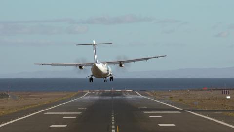 Jetliner landing on runway by the sea Footage