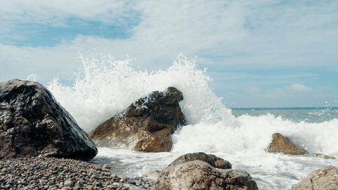 Panoramic shot from the sky to sea waves crashing on stones and spraying in Slow Footage