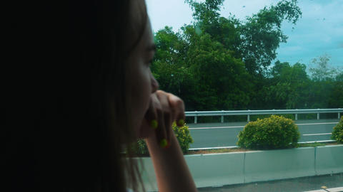A young woman sitting in the bus and looking in the window - looking at the road Live Action