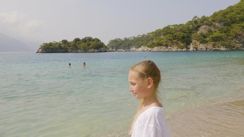 Portrait teenager girl in white dress on blue sea and green mountain landscape Footage