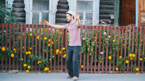 A russian man dancing russian folk dance by the fence with flowers Live Action