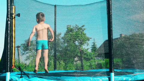 A child jumps on a trampoline outdoors HD Footage