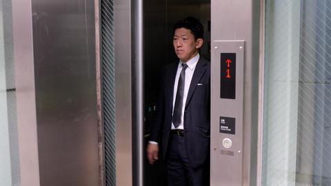 Japanese businessman taking an elevator Live Action