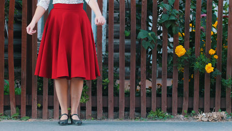 A woman in long red skirt dancing by the fence on the street in the village - Live Action