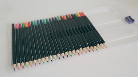 Man lays out colored graphite pencils in pencil case HD Footage