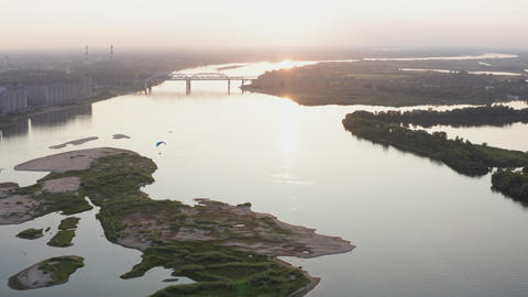 Parasail wing flying on golden sunset horizon landscape. Paraplane flying over river on city Footage