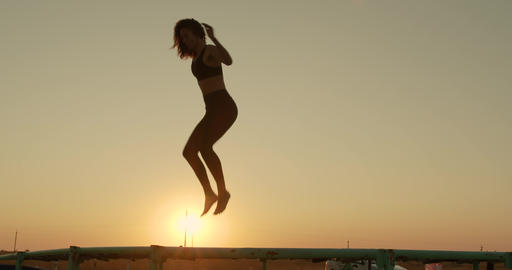 The girl jumps on trampoline in sunset sunlight on the beach Footage