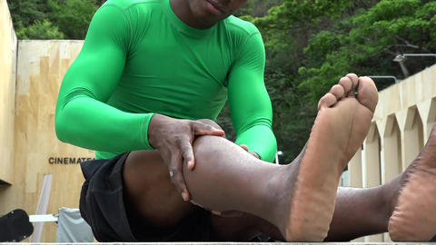 African Athlete Massaging Muscles Live Action