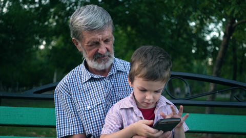 Senior grandfather and grandson are sitting on a bench in the park and playing Footage