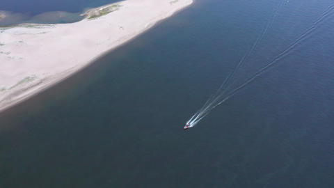 Drone view boat sailing in blue sea water. Motor boat floating on transparent lake water. Top view Footage