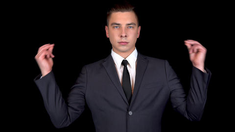 Young businessman snaps fingers on two hands. Man in a black suit on a black Footage