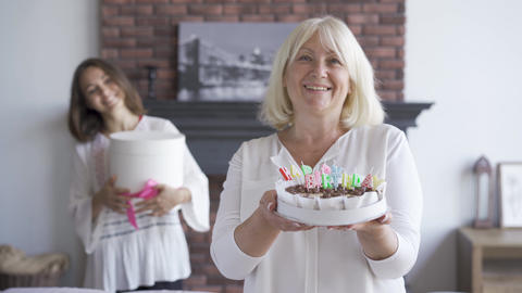 Happy senior woman showing a cake to the camera. Smiling young woman standing Footage