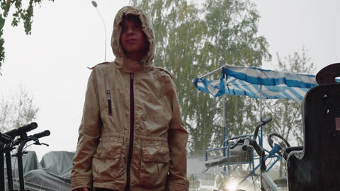 Teenager boy in hood jacket under summer rain in summer city. Portrait boy Live Action