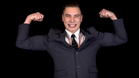 Young businessman shows biceps in his arms. Man in a black suit on a black Live Action