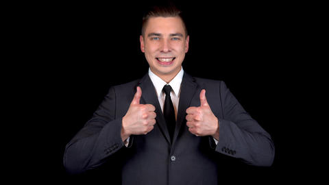 Young businessman shows like with both hands. Man in a black suit on a black Footage
