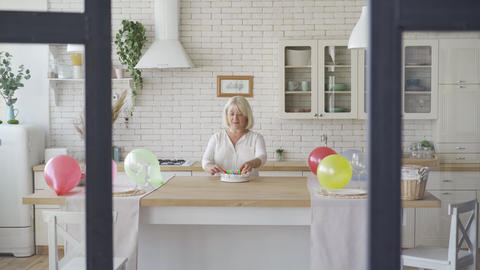 Senior woman preparing cake for her child or grandchild. Birthday celebration Footage