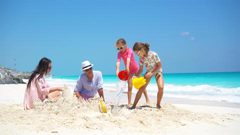 Family of four making sand castle at tropical beach Footage