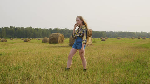 Country girl in checkered shirt and jeans short posing on country field in Footage