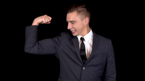 Young businessman shows biceps on his arm. Man in a black suit on a black Footage