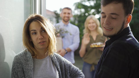 Young married couple meeting annoying guests standing at doors. Friendly Live Action