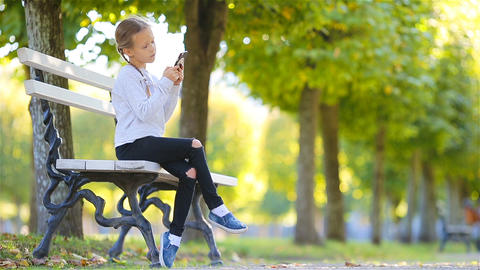 Adorable little girl at beautiful autumn day outdoors. Cute kid on the bench in Footage