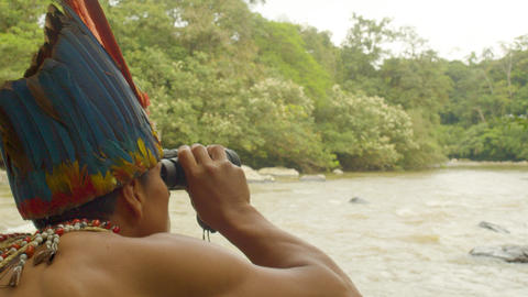 Amazonian Indigenous Man Watching Through A Binocular A Person In A Kayak Footage