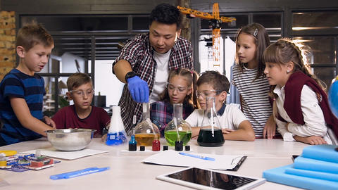 Asian science teacher with kids in lab class working about experiment by puts Footage
