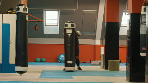 A man bodybuilder puts up the punching bag from the ground and putting it on his Live Action