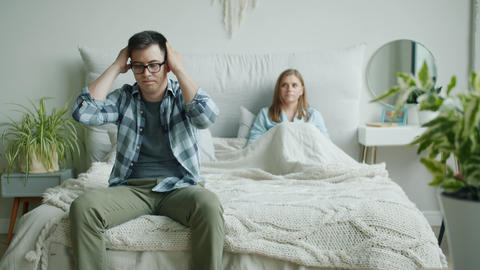 Unhappy man sitting on bed touching sad face while angry wife yelling at home Live Action