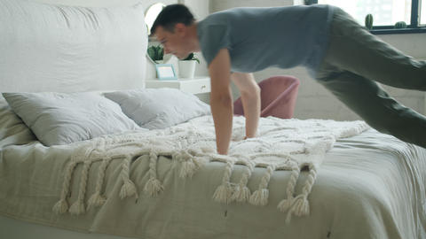 Slow motion of tired guy jumping in double bed at home and sleeping alone Footage