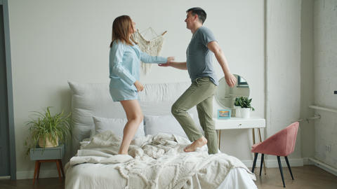 Man and woman couple dancing on bed at home enjoying music and relationship Live Action
