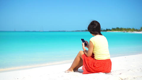 Young woman use phone during tropical beach vacation. Tourist using mobile Live Action