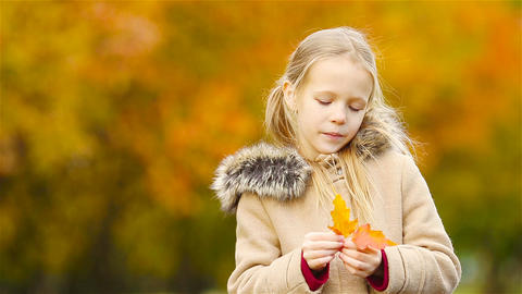 Portrait of adorable little girl outdoors at beautiful warm day with yellow leaf Footage