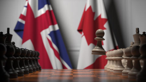Chess game against flags of Great Britain and Canada. Political competition Live Action