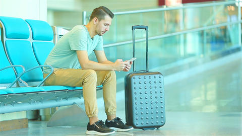 Young man in an airport lounge waiting for flight aircraft. Caucasian man with Footage