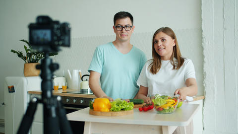 Man and woman recording video for vlog in kitchen showing vegetable using camera Live Action
