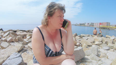 Elderly woman speaks on a smartphone Footage