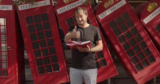 Smiling man showing thumbs up, standing against British telephone, studying Live Action