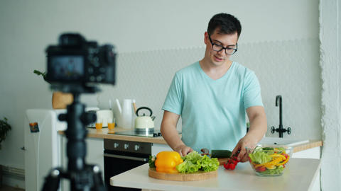 Young man vlogger recording video about organic food in kitchen at home Live Action