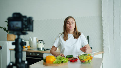 Slow motion of pretty lady recording video about vegetables in kitchen at home Footage