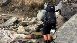 Hiker backpack cross mountain stones river. Himalayas Nepal HD video Footage