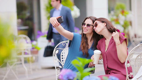 Two young girls taking selfie with smart phone at the outdoors cafe. Two women Live Action