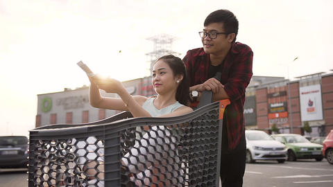 Cheerful carefree vietnamese couple scattering money at the shopping mall Live Action