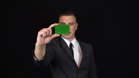 A young businessman in a suit holds a bank card in hand. Isolated black Footage