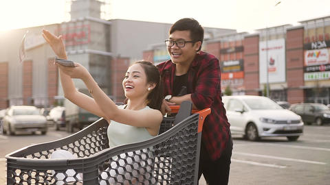 Attractive smiling asian guy being pushed in front of him market trolley with Live Action